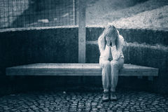 Grunge sad woman on wooden bench Stock Images