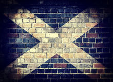 Grunge Scotland flag on a brick wall. Desaturated Scottish flag on a brick wall background with a dark vignette royalty free stock photography