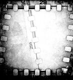 Grunge scratched dirty film strip background with reel. Royalty Free Stock Images