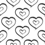 Grunge seamless pattern with hand painted black hearts. Stock Images