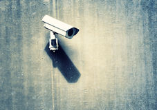 Grunge security camera with shadow. On the public cement concrete wall background Royalty Free Stock Photography