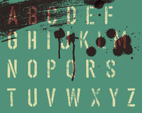 Grunge stencil alphabet with drops and streaks Royalty Free Stock Images