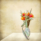 Grunge stil life, vase of tulips on a table. A well lit interior with a minimalist domestic scene: a glass vase full of red and yellow tulips royalty free stock photography