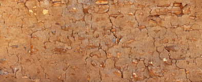 Grunge stone wall covered with clay plaster.  Stock Photos