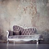 Grunge Styled Interior. Beautiful sofa in classical style on a background of textured walls Stock Image