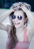 Grunge styled young brunette in sunglasses. Stock Image