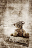 Grunge teddy bear. Grunge background with fur teddy bear in handmade hat, sitting on quilts and space for text Royalty Free Stock Image