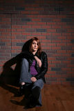 Grunge teen lounging in front of brick wall. Grunge style teen with auburn hair sitting in front of brick wall Stock Image