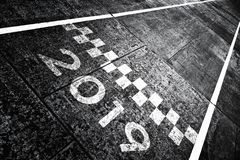 Start pattern line sign with 2019. Grunge textured start pattern line sign with number 2019 on the asphalt road stock images