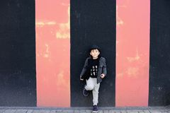 Grunge textured wall and fashion little boy. Fashionable boy standing in front of grunge wall with stripes, wearing wool jacket and a hat Royalty Free Stock Photos