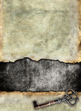 Grunge torn surface with antique key. Vintage background Royalty Free Stock Photos