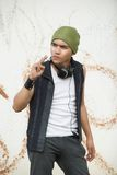 Grunge urban youth. Young Hispanic rapper dude in urban casual grunge clothing or funky fashion with cap, headphones and cigarette hanging out against background Stock Photography