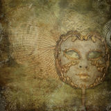 Grunge vintage background with mask. A retro wallpaper with venetian mask and golden decorations Stock Images