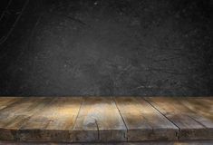 Grunge vintage wooden board table in front of black textured background Stock Photography