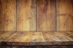 Grunge vintage wooden board table in front of old wooden background. Ready for product display montages Royalty Free Stock Photos