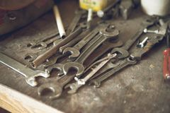 Grunge, vintage wooden workbench with rustic old metal wrenches of different measures lying. Old toolbox background. View from top royalty free stock images