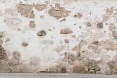 Grunge wall background. Old brick and stone wall with bright abandoned plaster. And pavement stock photos