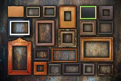 Grunge wall full of old frames Stock Photography