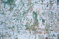 Grunge wall texture background. Paint cracking off dark wall with rust underneath. Stock Photos