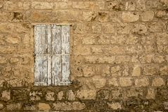 Grunge Weathered closed Window in old abandoned stone house wall. Grunge Weathered Window Shutter closed in old abandoned stone house stock images