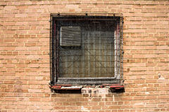 Grunge wired up window and brick wall. Detail Stock Photo