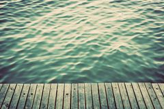 Grunge wood boards of a pier over ocean with rippling waves. Vintage Stock Photos