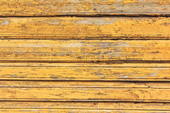 Grunge wood wall with cracks and peeling paint in old house. Yellow textured background Stock Photography