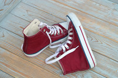 Grunge wooden background with red and white used vintage canvas sneakers Stock Image