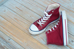 Grunge wooden background with red and white used vintage canvas sneakers Stock Photos