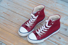 Grunge wooden background with red and white used vintage canvas sneakers Royalty Free Stock Photos