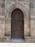 Grunge wooden ornate aged vaulted arched door on exterior decorated stone bricks Stock Photo