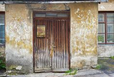 Wooden plank door with post box, dirty stucco wall background Royalty Free Stock Image