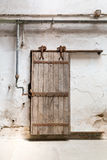 Grunge wooden roller door in prison cell. Royalty Free Stock Images