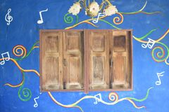 Grunge wooden window on blue music notes wall Royalty Free Stock Photos