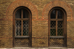 Grunge wooden windows on brick wall old windows on the brick wall. Grunge wooden window on brick wall old windows on the brick wall in Chernivtsi University Royalty Free Stock Image