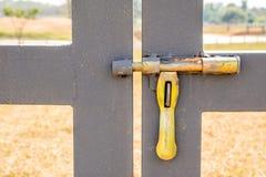 Grunge yellow bolt of entrance door in Farmland. Royalty Free Stock Photos