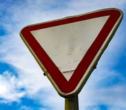 Grunge yield road sign. Against a blue cloudy skyn royalty free stock image