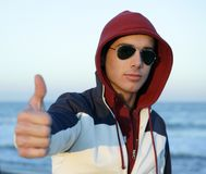 Grunge young man with hood at the beach. Grunge young man with hood and sunglasses at the beach Stock Photos