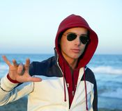 Grunge young man with hood at the beach. Grunge young man with hood and sunglasses at the beach Royalty Free Stock Images