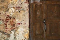 Grungeachtergrond - schurftige muur met barsten, oude houten deur Stock Afbeeldingen
