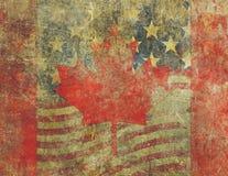 Grungeamerikanen och den kanadensiska flaggan planlägger strängt urblekt Arkivfoto
