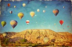 Grungebeeld van kleurrijke hete luchtballons tegen blauwe hemel in C Stock Afbeeldingen