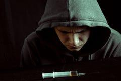 Grungebild av en deprimerad knarkare som ser en injektionsspruta och droger Royaltyfri Foto