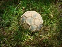 Grungefotboll- eller fotbollboll på en grön gräsmatta Royaltyfria Bilder
