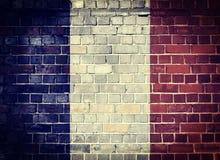 GrungeFrankrike flagga på en tegelstenvägg Arkivfoto
