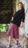 Grungemanier: mooi jong meisje in geruite rok en blousetribunes achter rooster royalty-vrije stock afbeelding