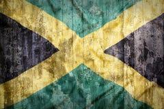 Grungestil av den Jamaica flaggan på en tegelstenvägg Royaltyfria Foton