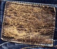 Grungy коричневый кожаный ярлык на голубой джинсовой ткани Стоковые Фотографии RF