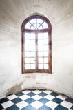 Grungy arched window inside old building. Grungy arched window with bright sunlight inside old building made of white stone with black-and-white tile on floor Royalty Free Stock Photo