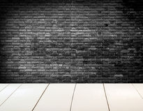 Grungy black and white textured brick wall with white wooden floor Stock Image